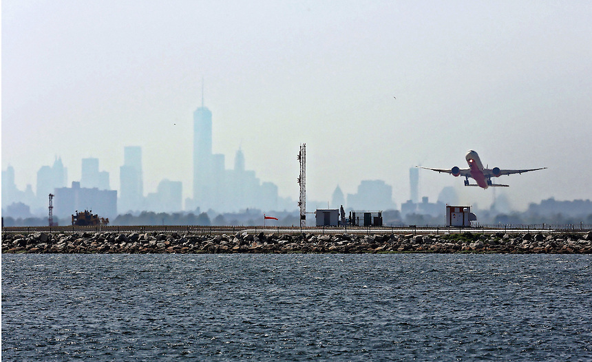 An aircraft takes off from JFK Airport against a backdrop of the hazy New York Skyline. photo by Trevor Collens