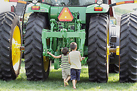Two boys examine a giant tractor at the NW Washington Fair. August 16, 2009 PHOTOS BY MERYL SCHENKER            .schenker IMG_9472.JPG