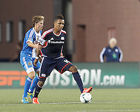 New England Revolution forward Juan Agudelo (10) dribbles as Philadelphia Union midfielder Brian Carroll (7) defends. In a Major League Soccer (MLS) match, the New England Revolution (dark blue) defeated Philadelphia Union (light blue), 5-1, at Gillette Stadium on August 25, 2013.