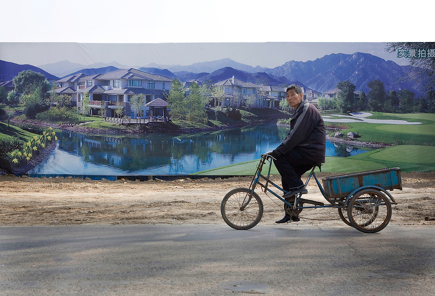 A man rides a tricycle past the advertisement for a new housing development in northern Beijing.  Suburbia is no longer an American phenomenon, a settlement pattern spreading across vast metropolitan areas. Head-spinning growth in China, Korea, India and other nations is turning the USA into a suburban laboratory for planners from these countries.