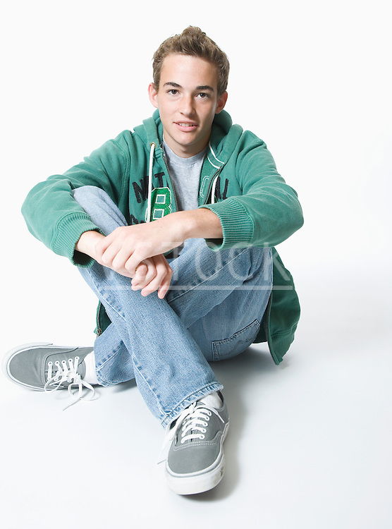 Teenage boy sitting cross-legged, portrait