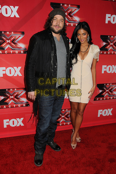 "Josh Krajcik and Nicole Scherzinger.FOX's ""The X Factor"" Press Conference held at CBS Television City, Los Angeles, California, USA..December 19th, 2011.full length jeans denim black jacket grey gray top beanie beard facial hair white cream dress cleavage low cut neckline  zip zipper.CAP/ADM/BP.©Byron Purvis/AdMedia/Capital Pictures."