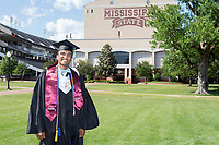 Student dressed in graduation regalia in the Junction.<br />  (photo by Beth Wynn / &copy; Mississippi State University)