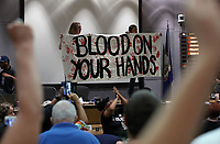 "Protestors stand on the city council desk holding a sign ""Blood on your hand"" after shutting down the Charlottesville City Council meeting Monday night in Charlottesville, Va. Photo/Andrew Shurtleff"