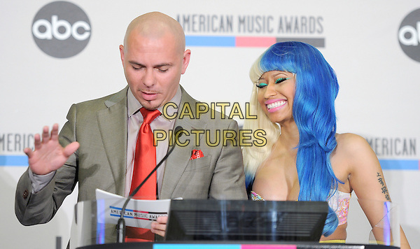 Pitbull (Armando Christian Perez) & Nicki Minaj.2011 American Music Awards Nominee Press Conference held at the JW Marriott LA Live Hotel, Los Angeles, California, USA..October 11th, 2011.half length top bra cleavage tattoo grey gray suit podium speech blue blonde hair dyed hand looking down smiling red tie.CAP/RKE/DVS.©DVS/RockinExposures/Capital Pictures.