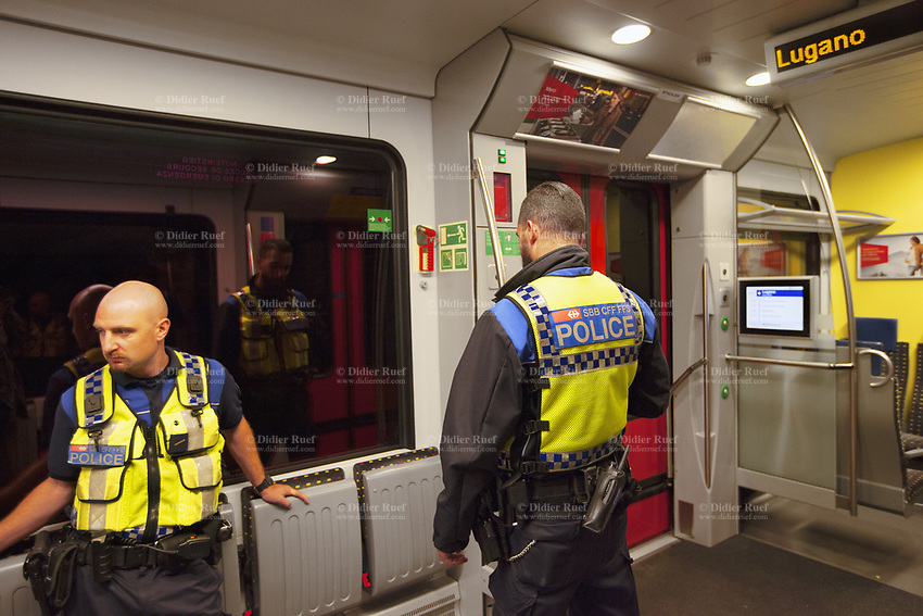 Switzerland. Canton Ticino. Lugano. Two police officers from TPO (Transport Police) late at night on a TILO train. TPO (Transport Police) is the Swiss Federal Railways Police. Swiss Federal Railways (German: Schweizerische Bundesbahnen (SBB), French: Chemins de fer fédéraux suisses (CFF), Italian: Ferrovie federali svizzere (FFS)) is the national railway company of Switzerland. It is usually referred to by the initials of its German, French and Italian names, as SBB CFF FFS. TILO (Treni Regionali Ticino Lombardia) creates efficient train connections between the towns in the canton Ticino.10.06.2017 © 2017 Didier Ruef