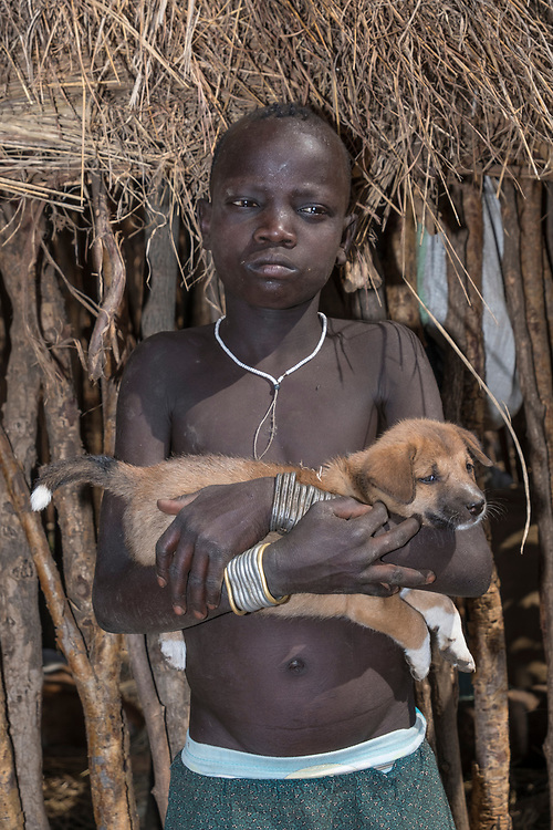 "In a Mursi village, characterized by pagan beliefs and associated body adornment, this boy & his puppy present a ""softer"" look."