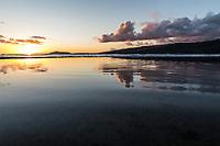 Tidal pools near Koko Head in Hawai'i Kai reflect a golden sunset over O'ahu; a distant Diamond Head is on the left.