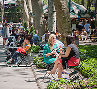 Crowds of visitors to Bryant Park in New York enjoy the 70 degree warm weather and a break from the rain on Thursday, May 12, 2016. While the warm weather continues the next couple of days may see showers. (© Richard B. Levine)