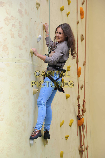 Louise Thompson.Walkers Crisp Deep Ridged Launch Climbing Wall at Truman Brewery, London, England..August 29th, 2012.full length grey gray top blue jeans denim harness rope sport exercise side.CAP/CAS.©Bob Cass/Capital Pictures.