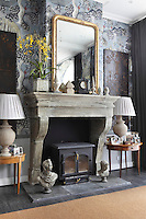Detail of the reclaimed antique fireplace in the sitting room with a gilt-framed mirror above and Verdure wallpaper by Zoffany