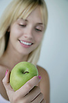 Close-up of a young woman holding a granny smith apple and smiling