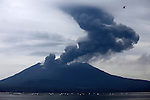Dark ash cloud rising into meteorological clouds following series of explosive eruptions of Sakurajima Volcano, Japan