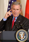 Washington, D.C. - June 24, 2005 -- United States President George W. Bush adjusts the earpiece where he gets the translation from Arabic to English as he listens to an Iraqi reporter's question during a joint press conference with Prime Minister Ibrahim al-Jaafari of Iraq in the East Room at the White House in Washington, D.C. on June 24, 2005.  They discussed the re-building of Iraq and refused to give a time-table for the withdrawal of United States forces.<br /> Credit: Ron Sachs / CNP