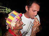 INDONESIA, Mentawai Islands, Kandui Resort, Mentawaian man lighting hand rolled cigarettes.