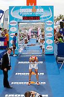 Triathlete Marcel Bischof finishes Ironman France 2012, Nice, France, 24 June 2012. Christian Estrosi, Mayor of Nice, looks on (left).