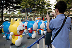 "July 16, 2014, Tokyo, Japan - People take pictures of Doraemon statues at Roppongi Hills on July 16, 2014. Sixty-six different statues of popular Japanese cartoon character Doraemon are lined up in front of the Mori Tower as a part of TV Asahi's ""Summer Station"" activities which will held from July 19 to August 24. (Photo by Rodrigo Reyes Marin/AFLO)"