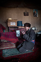 An old Kyrgyz man prays in his home. Kyrgyz are Sunni muslim but, because of the remoteness of their homeland, do not have access to Mosque...In and around the campment of Kyzyl Qorum, campment of the former deceased Khan, Abdul Rashid Khan..Trekking with yak caravan through the Little Pamir where the Afghan Kyrgyz community live all year, on the borders of China, Tajikistan and Pakistan.