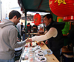 A Dublin shopper buys Sushi from a Japanese-run stall at the Saturday Market at Meeting House Square, in the heart of the popular Temple Bar District.