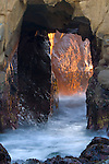 Sunset light and waves coming through hole in coastal rock at Pfeiffer Beach, Big Sur, California
