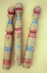 Three vintage childrens wooden skittles with scuffed blue and red painted stripes lying on antique paper