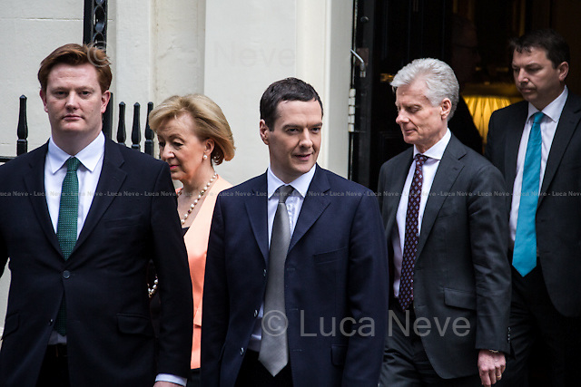 """London, 18/03/2015. UK Chancellor of the Exchequer, George Osborne (followed by his team) shows the """"red box"""" (Budget Box) containing the Budget for the fiscal year 2015."""