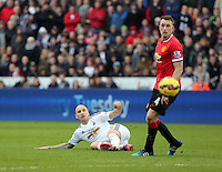 SWANSEA, WALES - FEBRUARY 21: L-R Jonjo Shelvey of Swansea passes the ball past Phil Jones of Manchester United during the Barclays Premier League match between Swansea City and Manchester United at Liberty Stadium on February 21, 2015 in Swansea, Wales.
