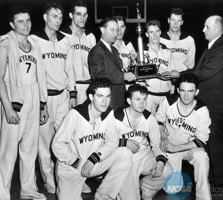 30 MAR 1943:  Coming form behind in the last few minutes of play, a snappy team from the University of Wyoming captured the NCAA Basketball Championship by swamping Georgetown 46-34, at Madison Square Garden 3/30/43. Here, coach Everett Shelton (center) receives the championship trophy from Professor Philip O. Badger, (far right), who is president of the NCAA, as members of the team look on. Front row L to R  Don Waite, Earl â??Shadowâ? Ray and Jim Reese. Back row L to R Jim Collins, Floyd Volker, Milo Komenich, Coach Everett Shelton, Lou Roney, Kenny Sailors, Jim Weir, Professor Philip O. Badger, President of the NCAA.  Photo Copyright University of Wyoming