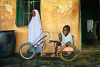 Polio victims Naja Atu Yusif, 15 (L), and Adamu Yusif, 13 (R), in the courtyard of their primary school in Kano. While Naja can limp, Adamu canít walk and has to use a tricycle to move around.
