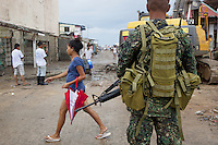 Philippines. Province Eastern Samar. Guiuan. Town centre . A soldier from the Phillipines's army with an M-16 weapon looks at a woman walking with a red umbrella and a group of men cleaning the debris from the streets. The 300 kph (or km/h) winds of typhoon Haiyan has blown and destroyed houses, ripped rooftops apart and smashed walls. The town of Guiuan was the first to face the fury of typhoon Haiyan when it barrelled into the Philippines on november 8 2013. Typhoon Haiyan, known as Typhoon Yolanda in the Philippines, was an exceptionally powerful tropical cyclone that devastated the country. Haiyan is also the strongest storm recorded at landfall in terms of wind speed (300 km per hour). The M-16 machine gun is a rifle adapted for semi-automatic and full-automatic fire . 28.11.13 © 2013 Didier Ruef