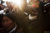 Ethnic Tibetan people pray as the sun comes out from behind the hill above a Buddhist laymen lodge where thousands of monks and nuns gather for morning chanting session during the Utmost Bliss Dharma Assembly, the last of the four Dharma assemblies at Larung Wuming Buddhist Institute in remote Sertar county, Garze Tibetan Autonomous Prefecture, Sichuan province, China November 1, 2015. The eight-day gathering starts every year around the 22rd of the ninth month on Tibetan calendar, the great day of Buddha's Descending from Tushita Heavens. The Larung Wuming Buddhist Institute, located some 3700 to 4000 metres above the sea level was founded in 1980 by Khenpo Jigme Phuntsok, an influential lama of Nyingma sect of Tibetan buddhism with only around 30 students but is now widely known as one of the biggest centres to study Tibetan Buddhism in the world. Picture taken November 1, 2015.  REUTERS/Damir Sagolj