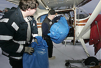 Saturday, Feb. 18, 2006  Anchorage, Alaska. Volunteer Iditarod Airforce pilot Joe Pendergrass loads straw into his Cessna plane prior to flying them  out to checkpoints along the trail.  Each musher is given one bale of straw at a checkpoint to bed their dogs down.