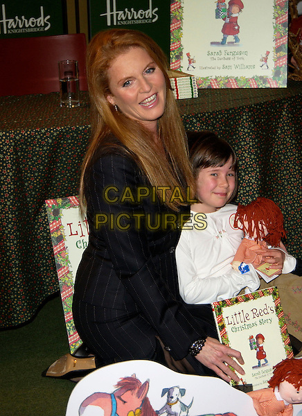 "SARAH FERGUSON, Duchess of York.Signs copies of her new book ""Little Red's Christmas Story"" ,Harrods , London 28  October 2004..half length pinstripe suit skirt girl child.Ref: PL.www.capitalpictures.com.sales@capitalpictures.com.©Capital Pictures.."