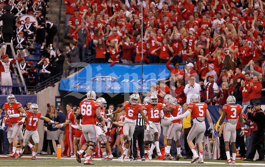 Ohio State Buckeyes quarterback Cardale Jones (12) celebrates with teammates after the first touchdown in the first quarter of the Big Ten Championship game at Lucas Oil Stadium in Indianapolis on Saturday, December 6, 2014. (Columbus Dispatch photo by Jonathan Quilter)