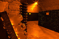 In the underground winecellar that is an old chalk quarry: thousands of bottles aging. A rack (pupitre) with clear bottles for the prestige cuvee standing on their heads waiting to be disgorged, Champagne Ruinart, Reims, Champagne, Marne, Ardennes, France, low light grainy grain