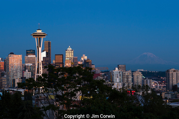 Focus on Space Needle with downtown buildings with sunset light on them with city lights, Seattle, Washington State USA