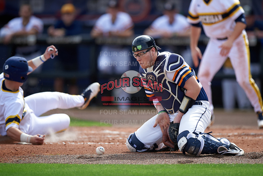 Canisius College Golden Griffins catcher Christ Conley (13) blocks a throw as Drew Lugbauer (17) slides home safely during the first game of a doubleheader against the Michigan Wolverines on February 20, 2016 at Tradition Field in St. Lucie, Florida.  Michigan defeated Canisius 6-2.  (Mike Janes/Four Seam Images)