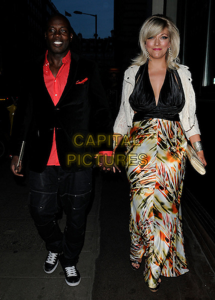MARTIN OFFIAH & GUEST .Attending the post-wedding party for Angellica Bell & Michael Underwood, The May Fair Hotel, London, England, UK, April 9th 2011..full length holding hands black jacket red shirt  jeans  print orange white maxi dress trainers couple .CAP/CAN.©Can Nguyen/Capital Pictures.