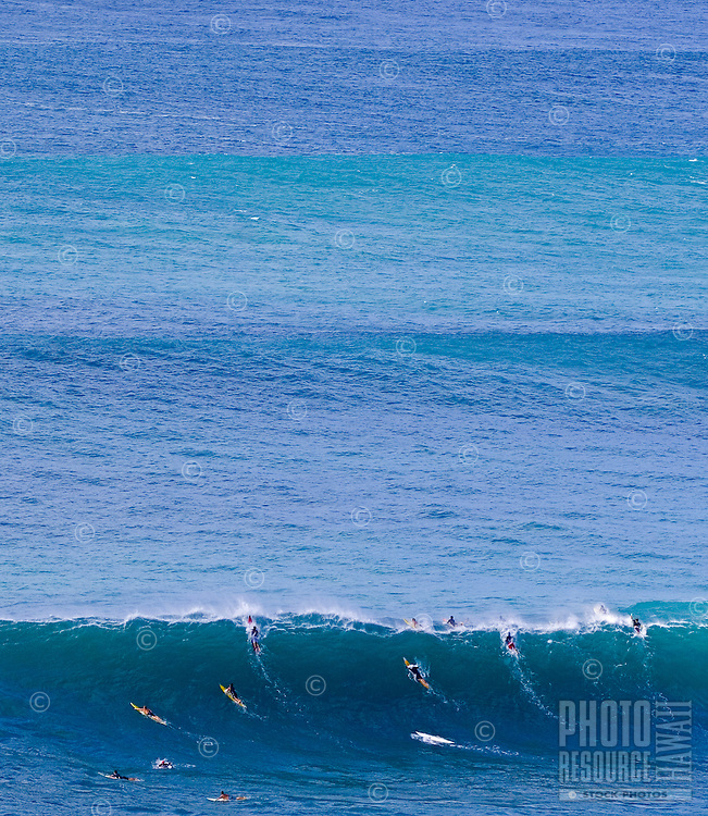 Surfers struggle over huge winter surf at Waimea Bay, on the North Shore of Oahu