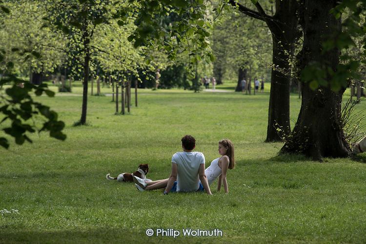 Young couple with a dog, Kensington Gardens, London.