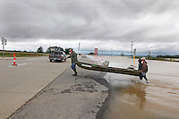 "From left, Steve Hyten, April Gensler and Josh Sherfield cross the eastbound lanes of US 60 after boating over the westbound lanes in Essex, MO on Wednesday, April 27, 2011. The group unsuccessfully tried to reach Gensler's home to collect some belongings left behind during evacuation the day before. ""The current was just too strong for our motor,"" said Gensler. ""If the current wasn't so bad, we would've made it."""