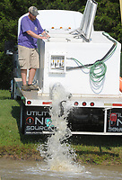 NWA Democrat-Gazette/DAVID GOTTSCHALK  Matt Gideon, with the Arkansas Game and Fish Commission, releases Friday, July 6, 2018, 460 pounds of channel catfish into the special events pond at the Washington County Juvenile Detention Center in Fayetteville. The University of Arkansas Division of Agriculture and Washington County Cooperative Extension Service, in a joint effort, are hosting the 4-H Fishing Derby 2018 this morning at the pond for Washington County 4H members and family.