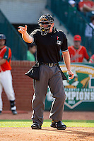 Home plate umpire Jake Wilburn makes a strike call during the South Atlantic League game between the Delmarva Shorebirds and the Greensboro Grasshoppers at NewBridge Bank Park on May 26, 2013 in Greensboro, North Carolina.  The Grasshoppers defeated the Shorebirds 11-2.  (Brian Westerholt/Four Seam Images)