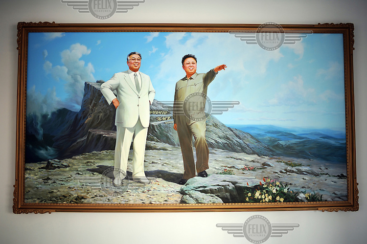 A propaganda painting on the wall in a textile factory featuring Eternal President Kim Il-sung (left) and Supreme Leader Kim Jong-il (right).