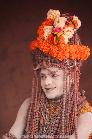 A Naga sadhu of the Juna Akhara with a fancy headdress of rudraksha bead malas, or prayer beads, and flowers.