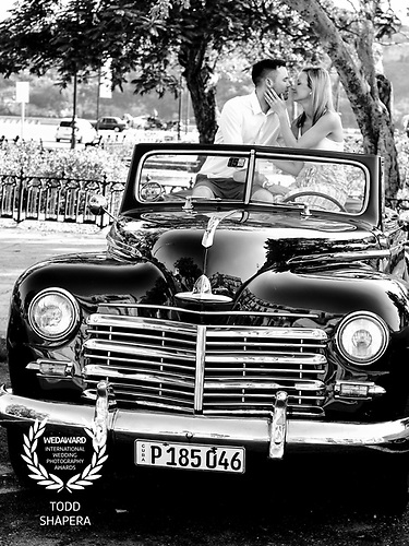 In Havana, Cuba, a couple enjoys engagement photography on the back seat of a classic convertible car.