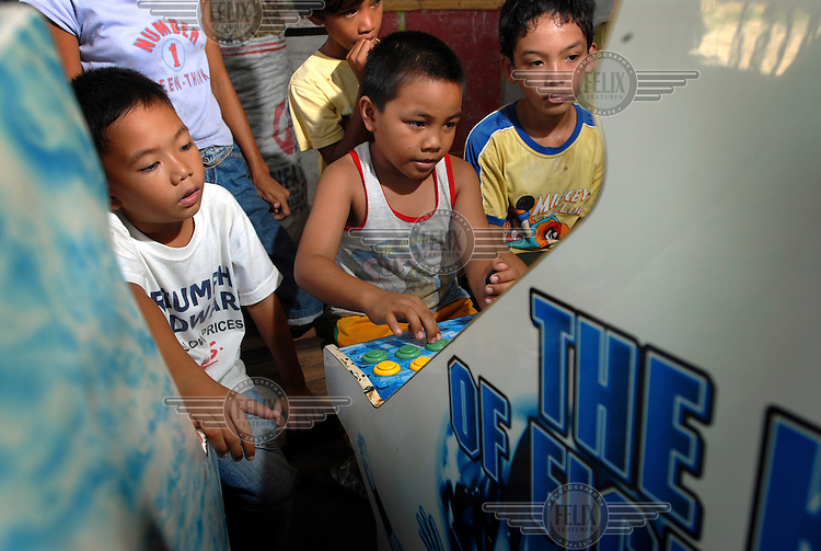 Children in a slum community playing on a video arcade machine located in a shop.