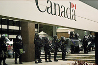 Police in riot gear, framed by a sign with the Canada logo, observing protesters at a meeting of the finance ministers of the G-7 nations in downtown Ottawa taken February 2002.