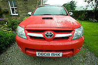 Red Toyota Hilux 4x4 outside a farmhouse, Lancashire...Copyright..John Eveson, Dinkling Green Farm, Whitewell, Clitheroe, Lancashire. BB7 3BN.01995 61280. 07973 482705.j.r.eveson@btinternet.com.www.johneveson.com