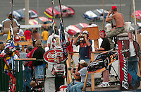 Race fans inside turns three and four snap pictures, cheer and talk on cell phones as the field of the NASCAR Busch Series Hershey's Kisses 300 passes at Daytona International Speedway. (Rick Wilson/The Florida Times-Union)